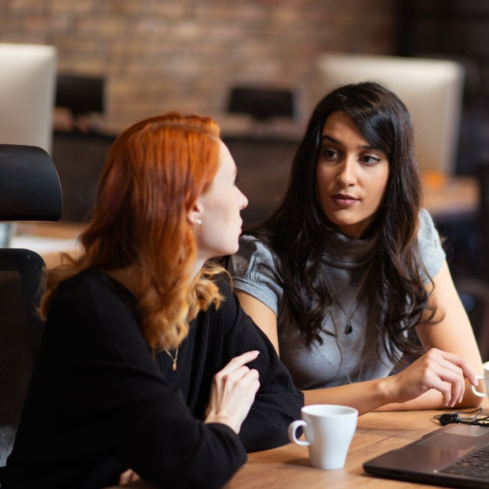 Two women having a conversation in an office